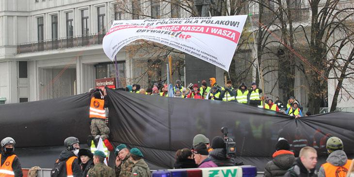 """Mężczyzna w kamizelce z logiem """"Straż Marszu Niepodległości"""" mocuje czarne płachty, które mają zasłonić pikietę """"Obywatele RP""""."""