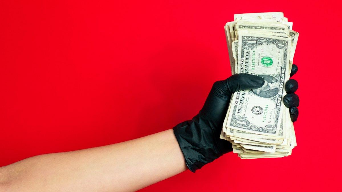 Ręka w czarnej rękawiczce trzymająca pieniądze